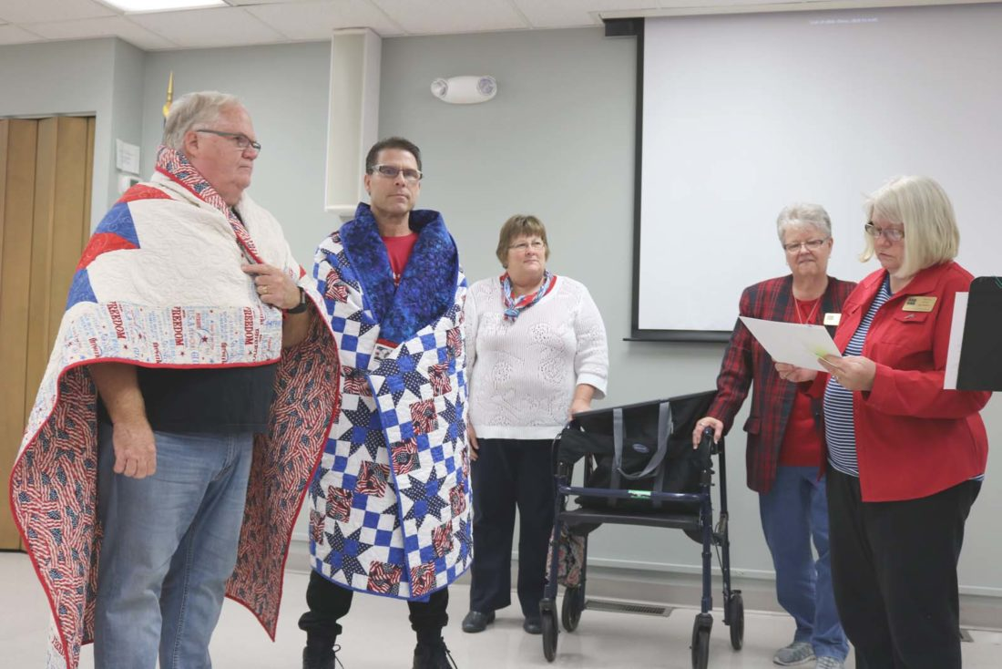 Dozens of Lennox Industries veterans enjoyed a luncheon Friday afternoon in honor of their service. U.S. Navy veteran Dave Huff and U.S. Marine Corps veteran Todd Frye were bequeathed with Quilts of Honor from the Central Iowa Quilt Sew-ciety. From left: Huff, Frye, Rosanne Anderson, Leslie Renaud and Marvis Drew