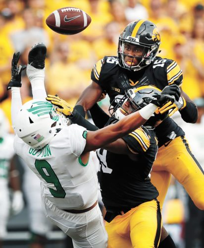 AP FILE PHOTO • Iowa defensive backs Miles Taylor, center, and Josh Jackson (15) break up a pass intended for North Texas wide receiver Jalen Guyton (9) during the second half of their college football game Sept. 16 in Iowa City.