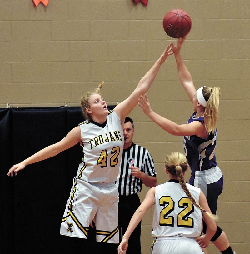 T-R PHOTO BY THORN COMPTON • West Marshall sophomore Teresa Disney (42) contests a shot from Colo-NESCO sophomore Rylee Purvis, right, during the Trojans' opening 61-36 victory over the Royals in State Center on Friday.