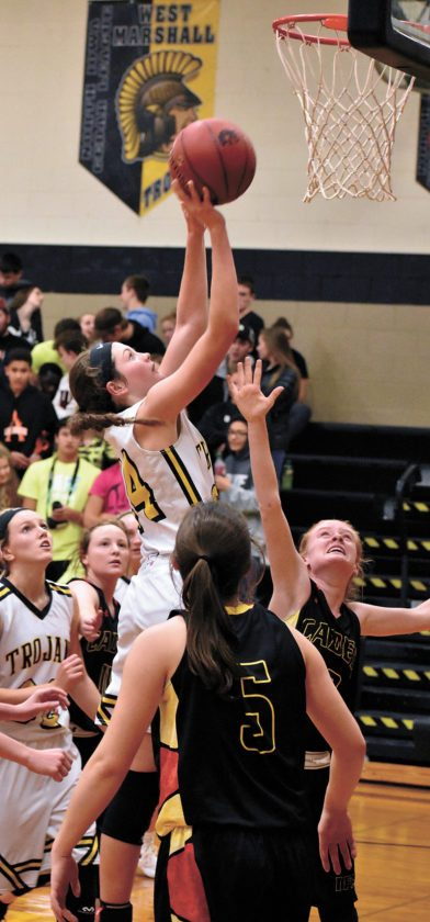 T-R PHOTO BY THORN COMPTON • West Marshall senior Isabelle Gradwell, center, puts up a shot after a rebound during the third quarter of the Trojans' 52-36 win over Iowa Falls-Alden on Tuesday night.