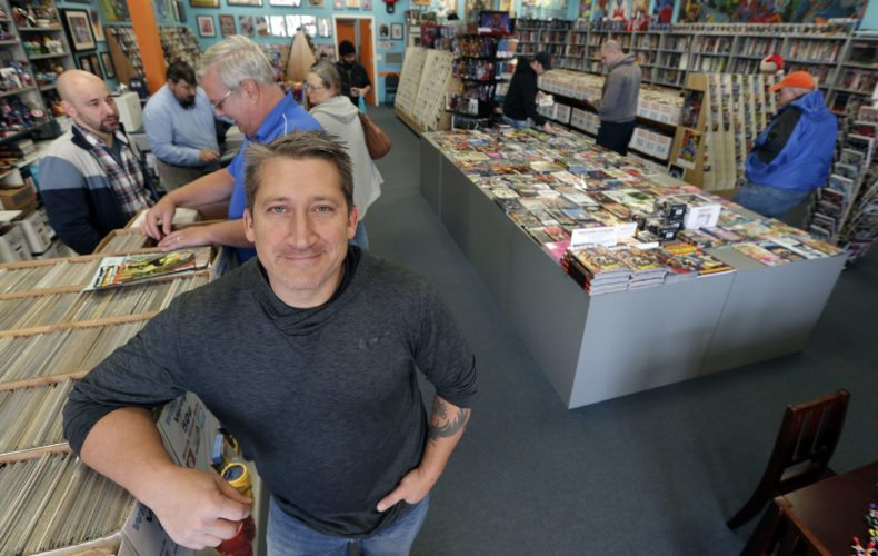 In this Wednesday, Nov. 8, 2017, photo, John Dudas, owner of Carol and John's Comic Book Shop, poses during New Comic Day in Cleveland. Some smaller retailers will tug at shoppers' heartstrings during the holidays, trying to create an emotional experience or connection that a big national chain might not provide. Dudas recently participated in Local Comic Shop Day, which he calls the comic book industry's equivalent of Black Friday. People lined up outside his store for limited-edition comics, and had a great time while they waited. (AP Photo/Tony Dejak)