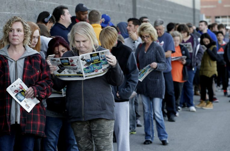 People wait in line for a Best Buy store to open for a Black Friday sale on Thanksgiving Day, Thursday, Nov. 23, 2017, in Overland Park, Kan. Shoppers are hitting the stores on Thanksgiving as retailers under pressure look for ways to poach shoppers from their rivals. (AP Photo/Charlie Riedel)
