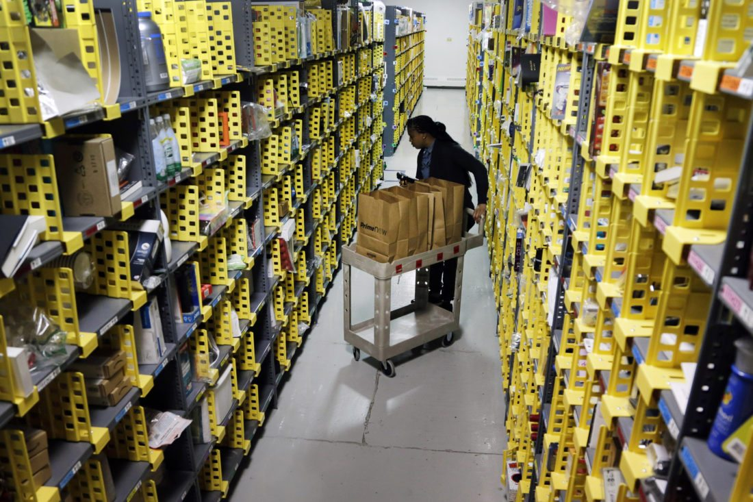FILE - In this Tuesday, Dec. 22, 2015, file photo, Amazon Prime employee Alicia Jackson hunts for items at the company's urban fulfillment facility that have been ordered by customers, in New York. Shoppers are expected to spend $6.6 billion on Cyber Monday, Nov. 27, 2017, up more than 16 percent from a year ago, according to Adobe Analytics, the research arm of software maker Adobe. And more people will be picking up their phones to shop: Web traffic from smartphones and tablets is expected to top desktop computers for the first time this year, Adobe said. (AP Photo/Mark Lennihan, File)
