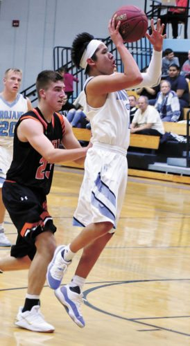 T-R PHOTO BY THORN COMPTON • South Tama guard Kaiden Buffalo, right, sends up a runner during the second half of the Trojans' 67-64 comeback victory over Grinnell in the team's opener in Tama on Monday night.