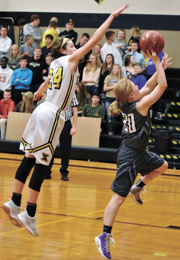 T-R PHOTO BY THORN COMPTON • West Marshall senior Isabelle Gradwell (24) attempts to block AGWSR junior Tori Brandt's shot from behind during the Cougars' win over the Trojans in State Center on Friday night.