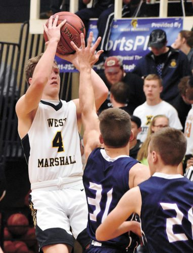 T-R PHOTY BY THORN COMPTON • West Marshall senior Beau Coberley (4) puts up a shot over AGWSR senior Alec Stahl during the third quarter of the Trojans' 71-35 win in their season opener over the Cougars.