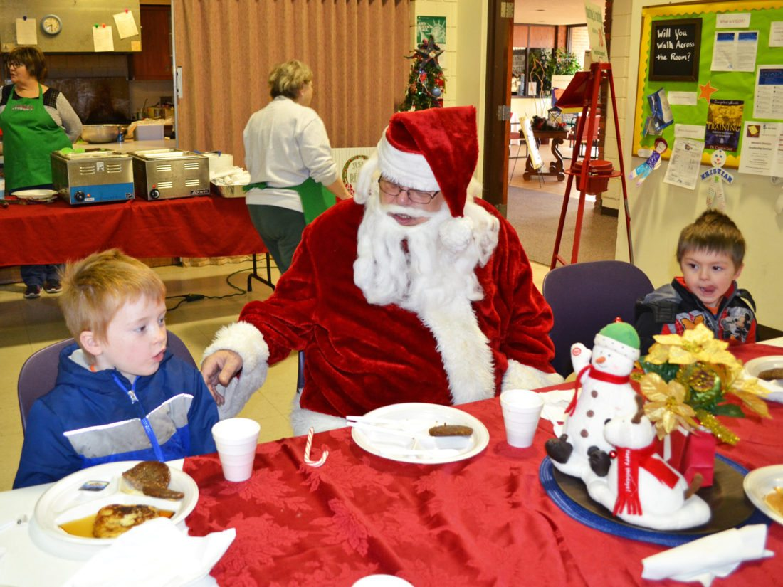Saturday morning at the Salvation Army, the public got the chance to eat breakfast with Santa Claus during a freewill donation meal, sponsored by the Salvation Army and the Kiwanis. Patrons dined on pancakes and sausage. Pictured are youngsters Christian Johnson, 6, left, and Hunter Johnson, 4, eating with Santa.