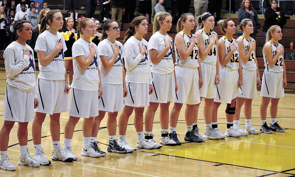 """T-R PHOTO BY THORN COMPTON • The BCLUW girls basketball team stands for the National Anthem, with the non-starters wearing warmup shirts that say """"#DarlaStrong"""" before the Comets' game against Montezuma on Monday night."""