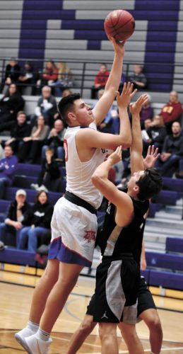 T-R PHOTO BY THORN COMPTON • Marshalltown senior Luke Appel, left, puts up a shot over Ankeny Centennial guard Zach Kluver to start the third quarter in the Bobcats' home-opening loss to the Jaguars on Tuesday night.