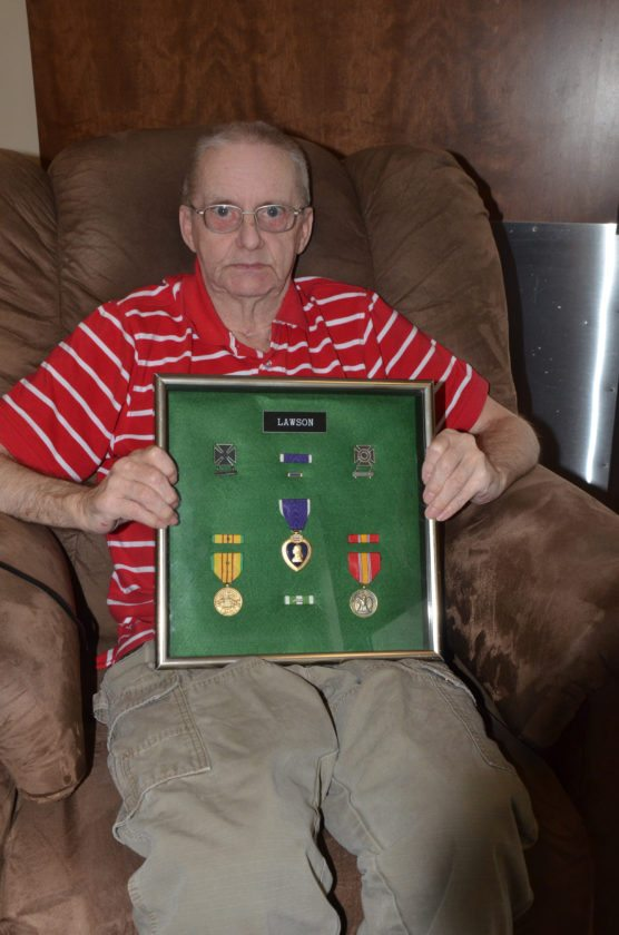 T-R PHOTO BY CHUCK FRIEND Le Grand native Darrell Lawson proudly poses with his medals earned while in Vietnam in the 1960s. Lawson was badly wounded in a roadside bomb explosion and suffers the effects of it to this day.