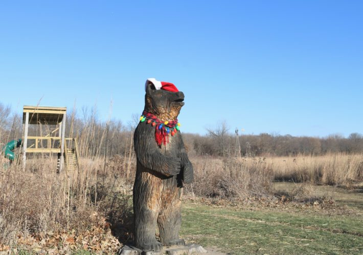 Unbeknownst to staff at Grimes Farm and Conservation Center, someone gave a festive makeover to one of the wood carvings at the outdoor playscape sometime late last week. The bear is now dressed for the season, with a Santa hat, holiday lights and a scarf to keep warm.
