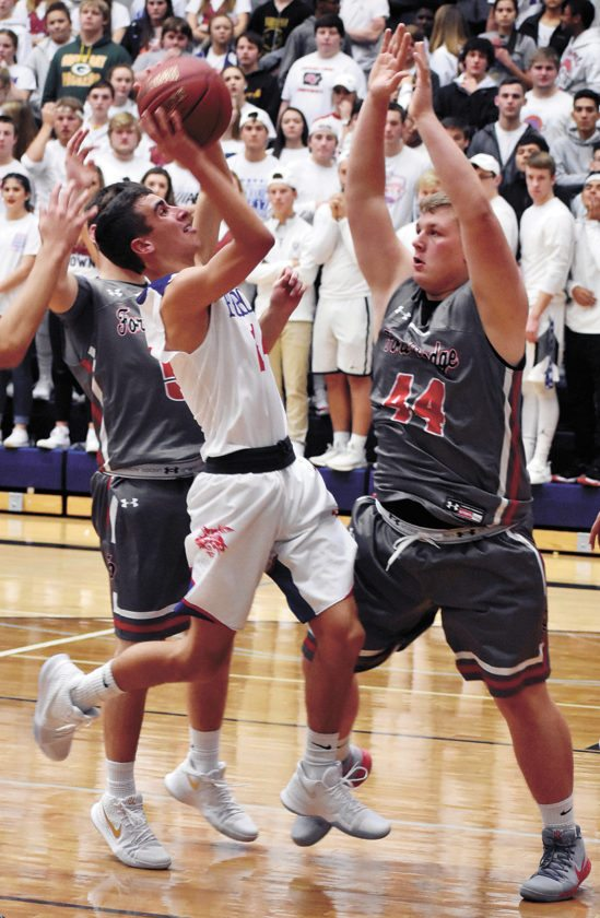 T-R PHOTO BY THORN COMPTON • Marshalltown sophomore Austin Shomo, left, drives in for a shot on Fort Dodge's Aaron Porter during the fourth quarter of the Bobcats' 65-55 loss to the Dodgers on Friday night.