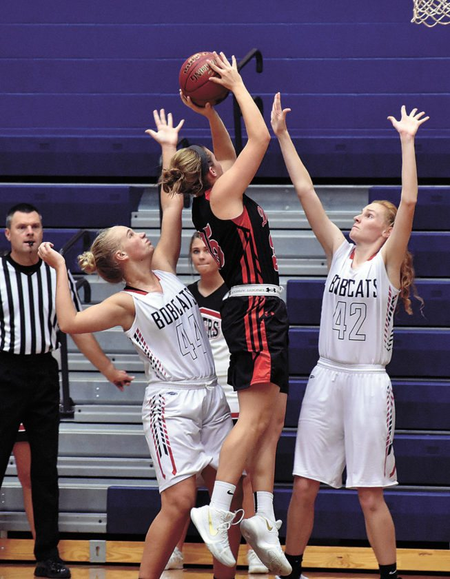 T-R PHOTO BY THORN COMPTON • Marshalltown defenders Grace Metzger (44) and Kassy Vest (42) defend the lane against Fort Dodge's Liza Van Zyl during the Bobcats' loss on Friday night to the Dodgers.