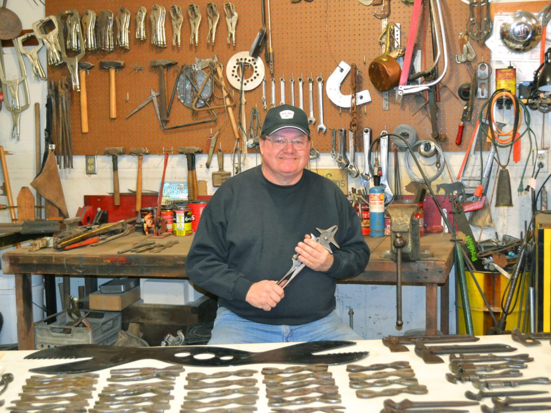 """Bill Roads of Haverhill has an impressive collection of thousands of antique tools and related farming and manufacturing implements. He favors equipment that was once made in Marshalltown, and ones designed by John R. Morris, his wife Judy's great-grandfather, who was a famed industrialist. He's pictured holding the """"Morris Wrench"""" the favorite piece in his collection."""