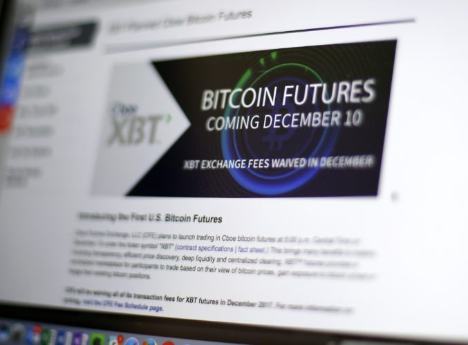 This Friday, Dec. 8, 2017, photo shows the Chicago Board Options Exchange website announcing that bitcoin futures will start trading on the CBOE on Sunday evening, Dec. 10. Bitcoin futures will start trading a week later on the Chicago Mercantile Exchange. (AP Photo/Kiichiro Sato)