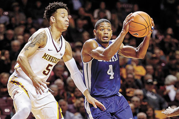 AP PHOTO • Drake guard De'Antae McMurray (4) looks to pass around Minnesota guard Amir Coffey (5) in the first half of a college basketball game Monday in Minneapolis.