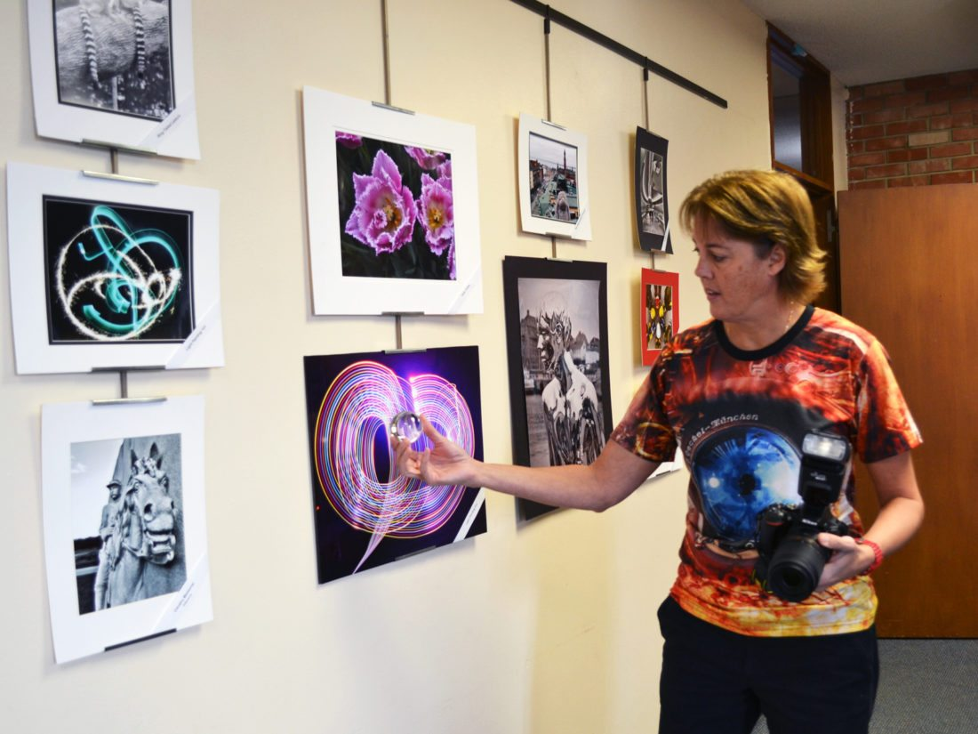 T-R PHOTO BY SARA JORDAN-HEINTZ Amy Snyder enjoys experimenting with props, lighting and subject matter when taking photographs. Here she demonstrates how holding a crystal decoration ball in front of a subject results in an inverted, magnified image being captured. Her photography is on display now through Feb. 1 inside Conference Room A in the Fisher Community Center, as part of the Central Iowa Camera Club's latest photo exhibit.