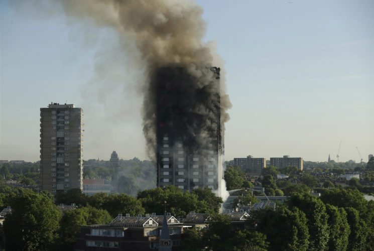 FILE- In this June 14, 2017, file photo, smoke rises from a high-rise apartment building on fire in London. Six months after flames enveloped the high-rise in London and prompted concerns about the safety of other buildings worldwide, a U.S.-based fire prevention group has developed a tool aimed at making buildings safer. The National Association of State Fire Marshals' research foundation announced that its free risk evaluation tool will be available on its website after Jan. 1, 2018. (AP Photo/Matt Dunham, File)