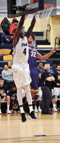 T-R PHOTO BY THORN COMPTON • Marshalltown Community College forward Mohamed Thiam (4) goes up for a dunk attempt while Iowa Lakes freshman Solomon Clayton contests during the second half of the Tigers' win over the Lakers on Wednesday night.