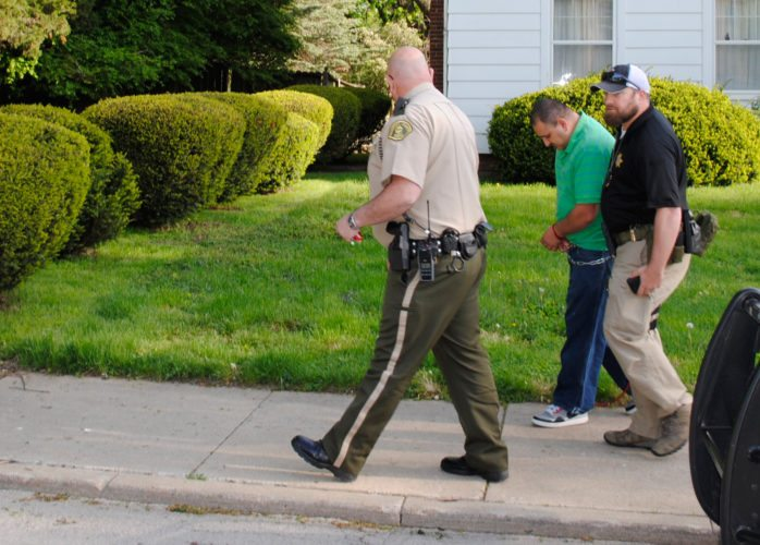 Law enforcement officials escort one of the suspects charged, Alejandro Hernandez, from his residence along State Street. He along with six other Marshalltown residents were convicted and sent to prison.