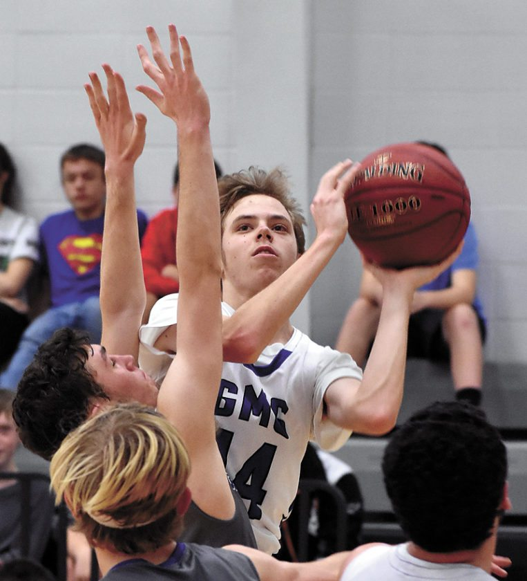 T-R PHOTO BY THORN COMPTON • GMG junior Aaron Fleming, top, hovers while readying a shot during the first half of the Wolverines' big win over Cedar Valley Christian on Monday.