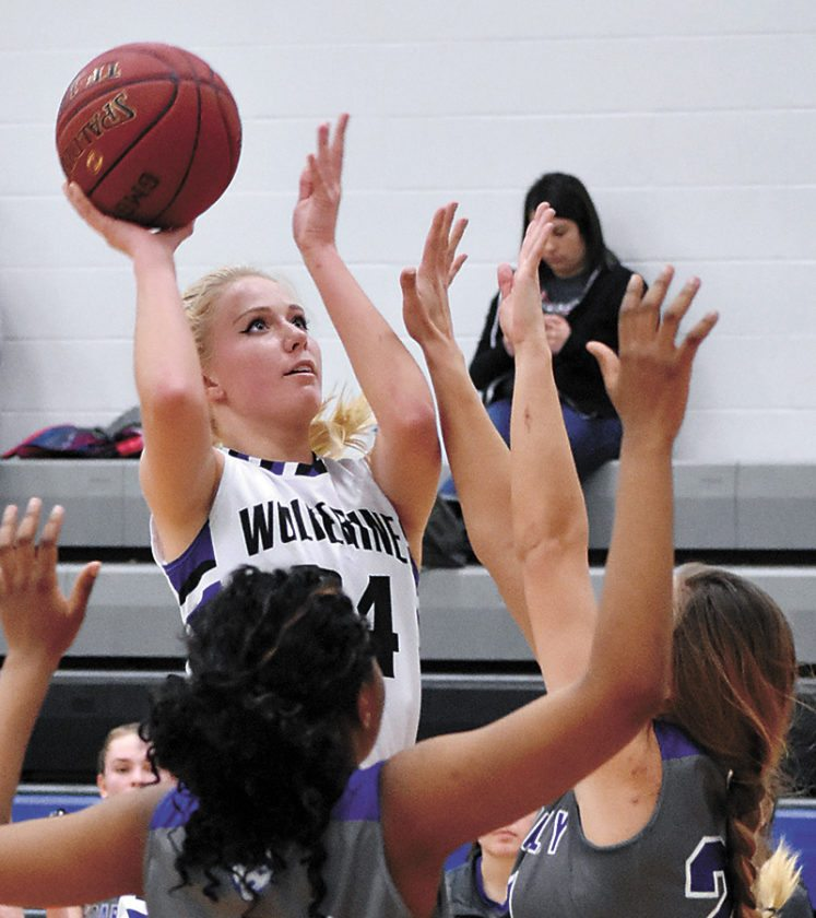 T-R PHOTO BY THORN COMPTON • GMG senior McKensie Vaske puts up a shot in the paint while Cedar Valley Christian defenders Candy Mafuta and Maggie Cach attempt to block during the first half of the Wolverines' loss to the Huskies on Monday.