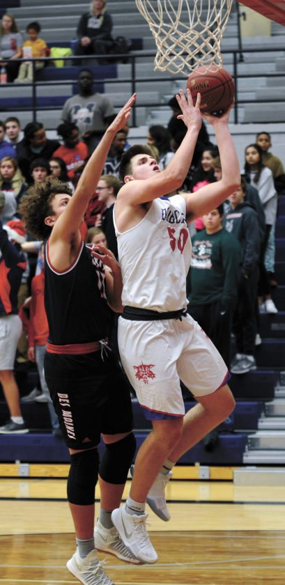T-R PHOTO BY ROSS THEDE • Bobcat senior Luke Appel (50) gets the hoop and the harm from Des Moines East's TK Dabner during the second half of Tuesday's game at the Roundhouse.
