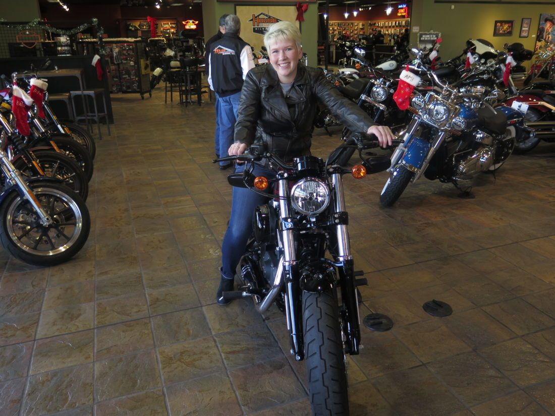 """In this Dec. 12, 2017, photo, Samantha Kay poses for a photo on a 2017 Harley Sportster Forty-Eight in Milwaukee's House of Harley. Kay took a riding course at the dealership as part of Harley-Davidson's """"Riding Academy,"""" an initiative the company hopes will help bring new customers. (AP Photo/Ivan Moreno)"""