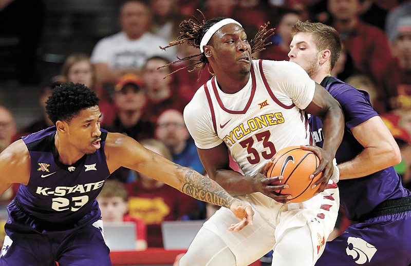 AP PHOTO • Iowa State's Solomon Young (33) drives between Kansas State's Amaad Wainright, left, and Dean Wade during the first half of their Big 12 Conference basketball game Friday night at Hilton Coliseum in Ames.