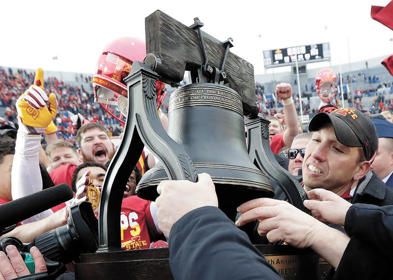 AP PHOTO • Iowa State head football coach Matt Campbell, right, is presented with his team's trophy after defeating Memphis in the Liberty Bowl on Saturday in Memphis, Tenn. Iowa State won 21-20.