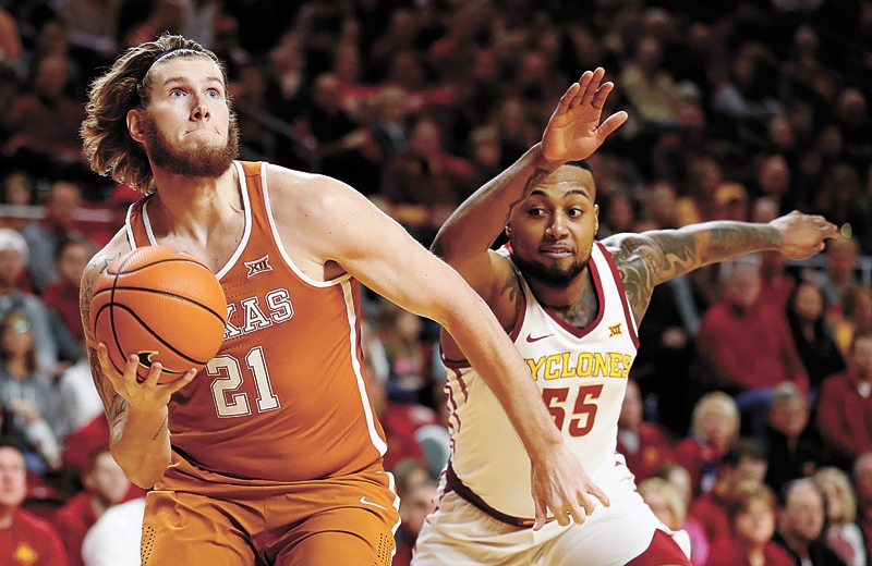 AP PHOTO • Texas forward Dylan Osetkowski (21) drives to the basket past Iowa State's Jeff Beverly (55) during the first half of a Big 12 Conference basketball game Monday night in Ames.