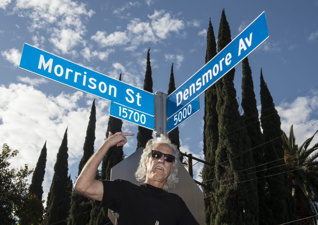 """John Densmore shows the new street sign during The second annual """"Day Of The Doors"""" event in Encino, Calif., on Thursday, Jan. 4, 2018. Los Angeles City Council member Paul Koretz unveils an intersecting street signs for Morrison Street and Densmore Avenue in Encino, in honor of founding band members Jim Morrison and John Densmore. (Ed Crisostomo/Los Angeles Daily News via AP)"""