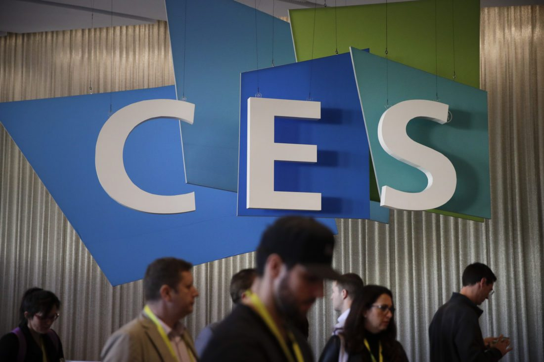 FILE - In this Friday, Jan. 6, 2017, file photo, show attendees walk past the CES sign at CES International in Las Vegas. As the 2018 CES gadget show kicks off in Las Vegas, manufacturers are expected to unveil new ways for consumers to control their products with voice commands over smart speakers such as Amazon Echo. (AP Photo/Jae C. Hong, File)