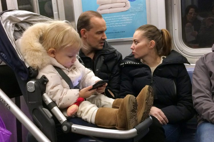 In this Dec. 17, 2017, photo, a baby girl plays with a mobile phone while riding in a New York subway. Two major Apple investors have urged the iPhone maker to take action to curb growing smartphone use among children, highlighting growing concern about the effects of gadgets and social media on youngsters. (AP Photo/Mark Lennihan)
