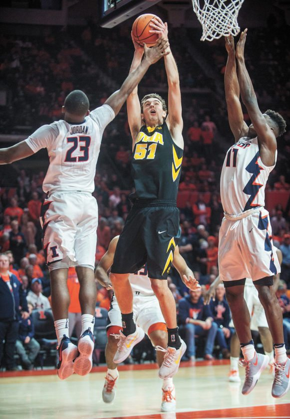 AP PHOTO • Iowa forward Nicholas Baer (51) goes up with a shot between Illinois defenders Aaron Jordan (23) and Greg Eboigbodin (11) during overtime of their Big Ten Conference basketball game Thursday in Champaign, Ill. Iowa won 104-97 in overtime.