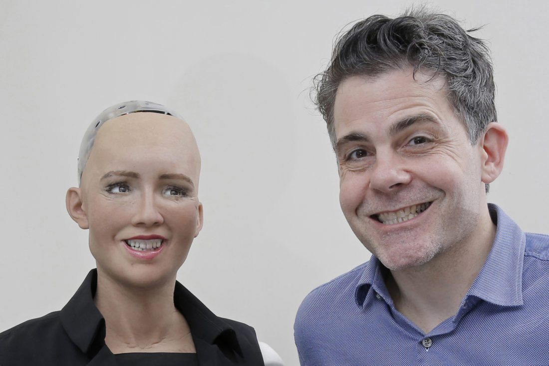 """In this Sept. 28, 2017, photo, David Hanson, the founder of Hanson Robotics, smiles with his company's flagship robot Sophia, a lifelike robot powered by artificial intelligence, for a photo in Hong Kong. Sophia is a creation of the Hong Kong-based startup working on bringing humanoid robots to the marketplace. Hanson envisions a future in which AI-powered robots evolve to become """"super-intelligent genius machines"""" that can help solve mankind's most challenging problems. (AP Photo/Kin Cheung)"""