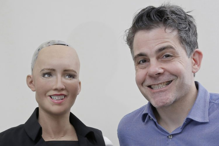 "In this Sept. 28, 2017, photo, David Hanson, the founder of Hanson Robotics, smiles with his company's flagship robot Sophia, a lifelike robot powered by artificial intelligence, for a photo in Hong Kong. Sophia is a creation of the Hong Kong-based startup working on bringing humanoid robots to the marketplace. Hanson envisions a future in which AI-powered robots evolve to become ""super-intelligent genius machines"" that can help solve mankind's most challenging problems. (AP Photo/Kin Cheung)"