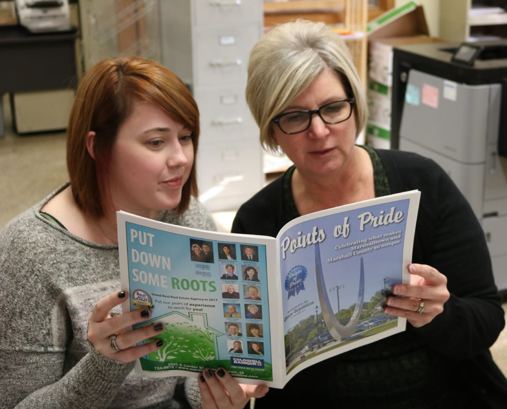 "T-R PHOTO BY JEFF HUTTON Times-Republican advertising staff members Candice Callaway, left, and Lynne Guldager, peruse the new ""Points of Pride"" magazine published by the T-R. The publication will be featured in this Sunday's edition."