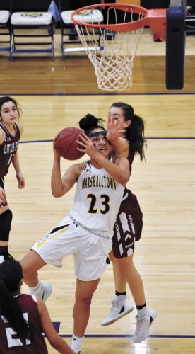 T-R PHOTO BY THORN COMPTON • Marshalltown Community College sophomore Loralei Siliga (23) drives hard to the basket despite contact from Little Priest Tribal College's Kristina Kemm during the Tigers' 74-57 defeat of the Warriors on Wednesday.
