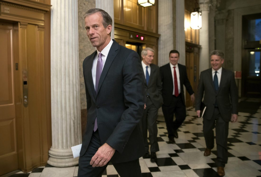 FILE - In this Dec. 18, 2017, file photo, Sen. John Thune, R-S.D., heads to a meeting at the Capitol in Washington. Key senators and farm groups are trying to fix a provision in the federal tax overhaul that gave an unexpected tax break to farmers who sell their crops to cooperatives instead of private buyers. The provision from Thune and John Hoeven, R-N.D., surfaced in the final days of the debate over the tax bill, which President Donald Trump signed last month. (AP Photo/J. Scott Applewhite, File)