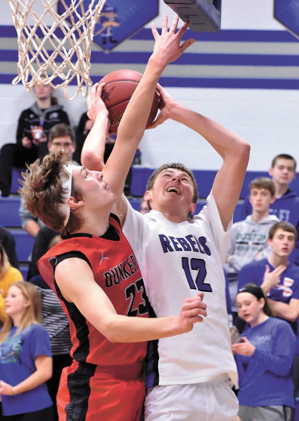 T-R PHOTO BY THORN COMPTON • Gladbrook-Reinbeck senior Caden Kickbush (12) takes the ball strong to the hoop while Dunkerton's Brady Happel attempts to contest the shot during the first half of the Rebels' win over the Raiders to end Dunkerton's unbeaten season.