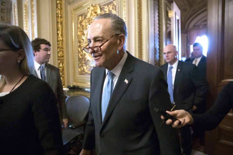 Senate Minority Leader Chuck Schumer, D-N.Y., heads to the chamber with fellow Democrats for a procedural vote aimed at reopening the government, at the Capitol in Washington, Monday, Jan. 22, 2018. (AP Photo/J. Scott Applewhite)
