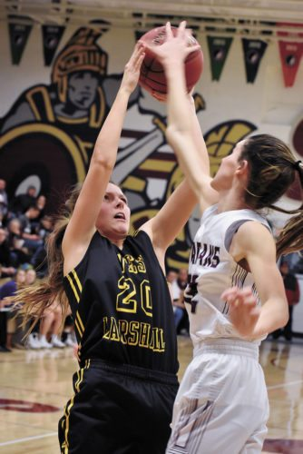 T-R PHOTO BY THORN COMPTON • Grundy Center junior Hailey Wallis, right, blocks a shot from West Marshall's Avril Sinning (20) during the Spartans' come-from-behind victory over the Trojans in Grundy Center on Tuesday.
