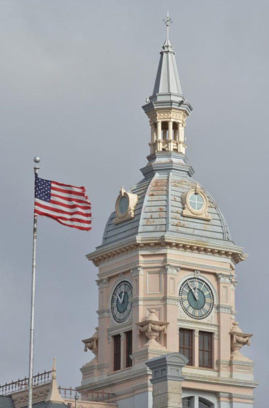 A stiff wind showcases the red, white and blue as the American flag waves in front of the Marshall County Courthouse.
