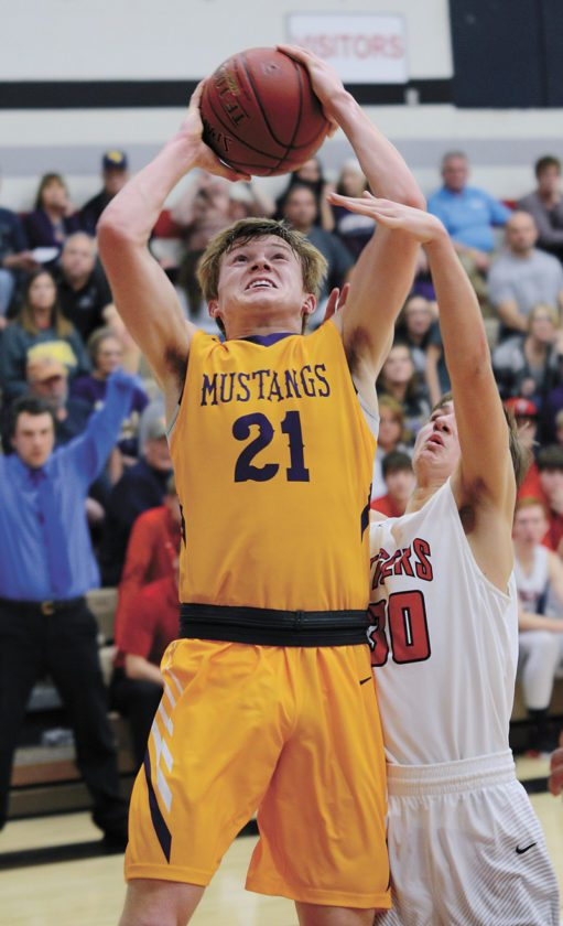 T-R PHOTO BY ROSS THEDE • East Marshall senior Zane Johnson (21)goes up for a basket in front of South Hardin's Gavin Ridout during the first half of their NICL West Division showdown Thursday in Eldora. Johnson scored a career-high 31 points as the Class 2A No. 10 Mustangs won 75-58.