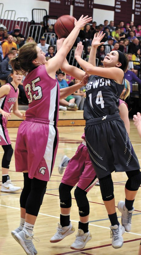 T-R PHOTO BY THORN COMPTON • AGWSR senior Mandy Willems (14) drives the lane while Grundy Center junior Kylie Willis makes contact during the fourth quarter of the Spartans' home win over the Cougars. Willems finished with a game-high 25 points, 16 of which came in the fourth quarter.