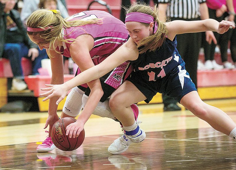 PHOTO BY CHRIS ZOELLER/THE GLOBE GAZETTE • Marshalltown junior Alyvia Chadderdon, right, and Mason City sophomore Anna Deets battle for a loose ball during Friday's CIML Iowa Conference girls' basketball game in Mason City. The Class 4A No. 7 Mohawks beat the Bobcats 74-34.