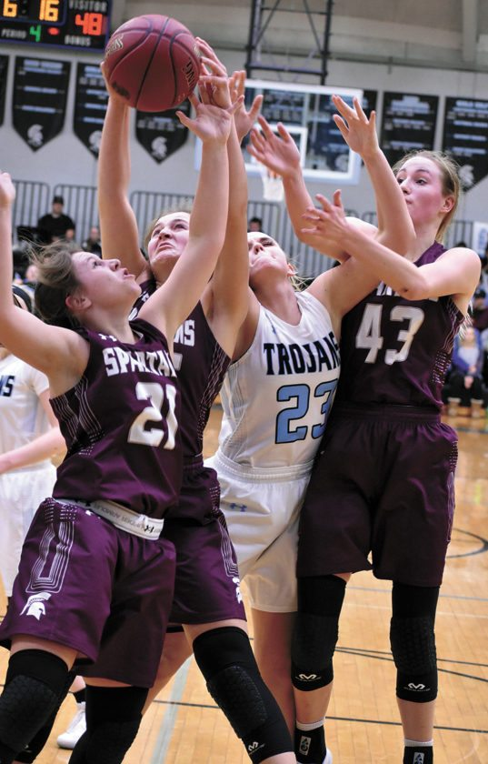 T-R PHOTO BY THORN COMPTON • Grundy Center players Sydney Mathews (21), Kylie Willis, middle, and Brooke Flater (43) fight with South Tama County's Madison Rohach (23) for a rebound in the second half of the Spartans' 62-52 victory over the Trojans in Tama on Thursday.