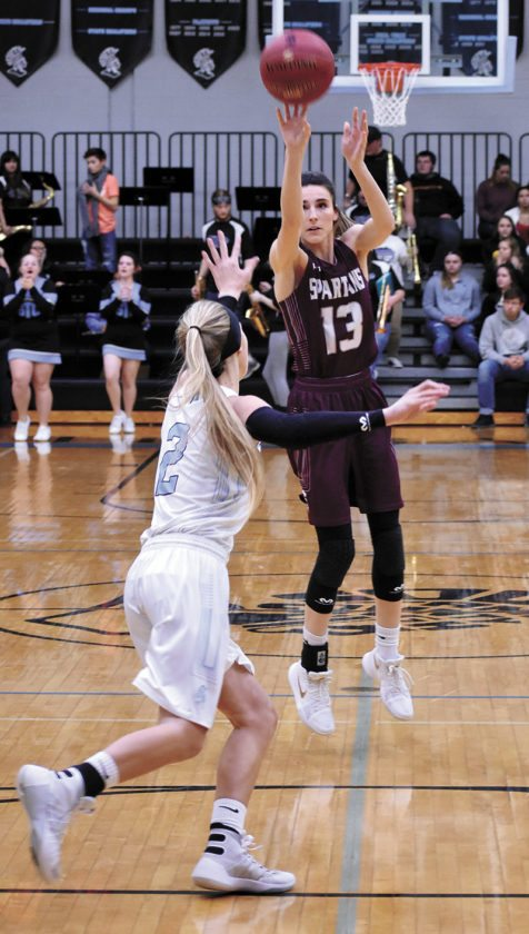 T-R PHOTO BY THORN COMPTON • Grundy Center junior Hailey Wallis (13) pulls up from behind the 3-point line while South Tama County senior Sadie Smith contests during the first quarter of the Spartans' win over the Trojans on Thursday. Wallis finished with a season-high 26 points in the win.