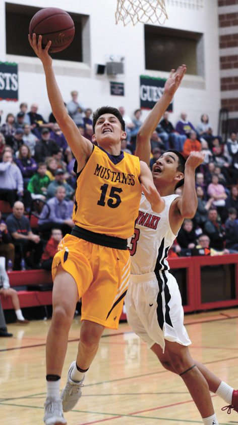 T-R PHOTO BY ROSS THEDE • East Marshall's Zach Finders (15) scores a fast-break layup in front of Meskwaki defender Taurice Grant during the first half of Thursday's game at Meskwaki Settlement School.